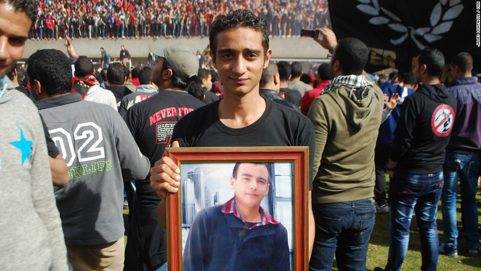 Many of the victims' families were also there, holding pictures of loved ones. Here one young fan holds a portrait of his best friend, who died in Port Said.