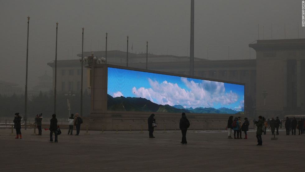 A video screen in Tiananmen Square shows blue skies amid the heavy smog on January 23.