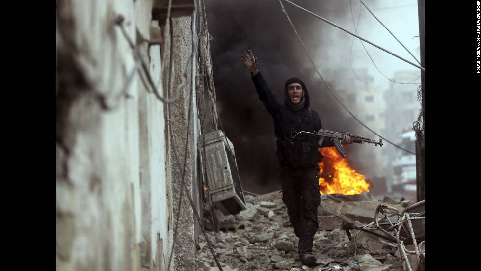 "Photographer Goran Tomasevic, <a href=""http://blogs.reuters.com/photographers-blog/2013/01/30/deadly-sniper-shot-through-the-lens/"" target=""_blank"">embedded with the Free Syrian Army</a>, captured an intense firefight and the death of a rebel fighter in Damascus on Wednesday, January 30. Here, a Free Syrian Army fighter gestures in front of a burning barricade during heavy fighting in the Ain Tarma neighborhood of Damascus."