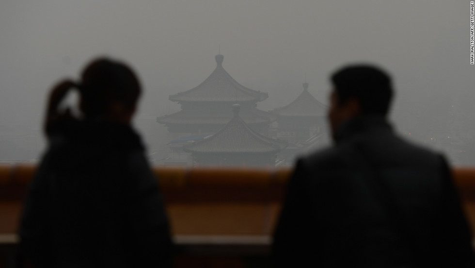 Chinese tourists look at the barely visible historic buildings in Jingshan Park.