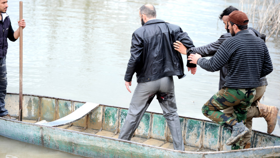 "A rebel leader is helped into a boat on Wednesday, January 30, by rebel fighters after he was injured during shelling by pro-Syrian forces.  The boat will transport them to Turkey near the northern Syrian town of Darkush. Click through to view images from the Syrian conflict from December and January, or <a href=""http://www.cnn.com/2012/12/04/middleeast/gallery/syria-unrest-november/index.html"">see photos from November</a>."