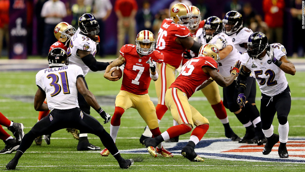Quarterback Colin Kaepernick of the 49ers runs with the ball in front of Ravens safety Bernard Pollard, No. 31.