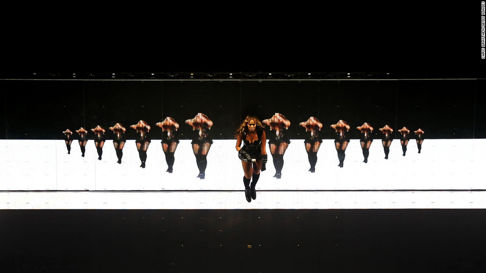 Beyonce dances in front of a screen on stage.