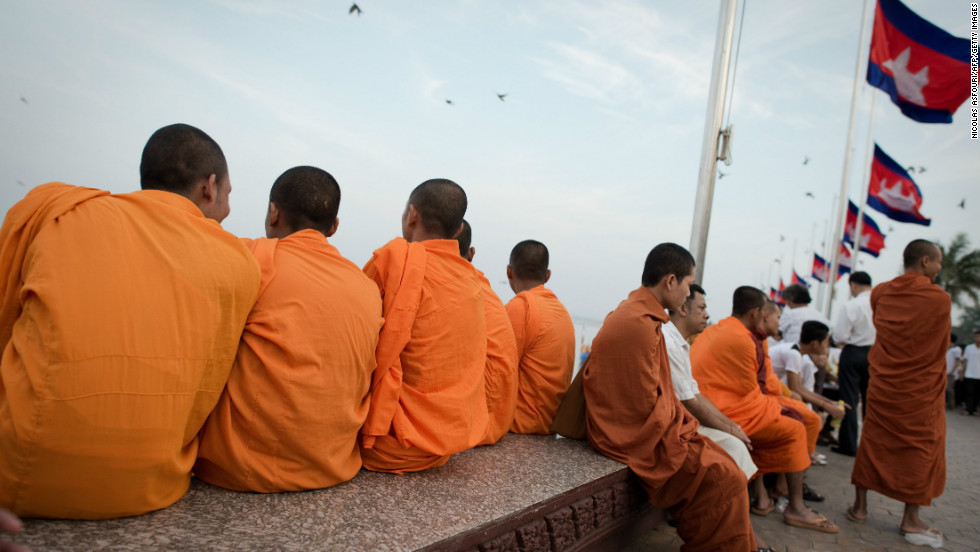 Cambodian Buddhist monks sit on the Mekong river bank as mourners gather to pray and pay their respects for the late former king on Sunday.