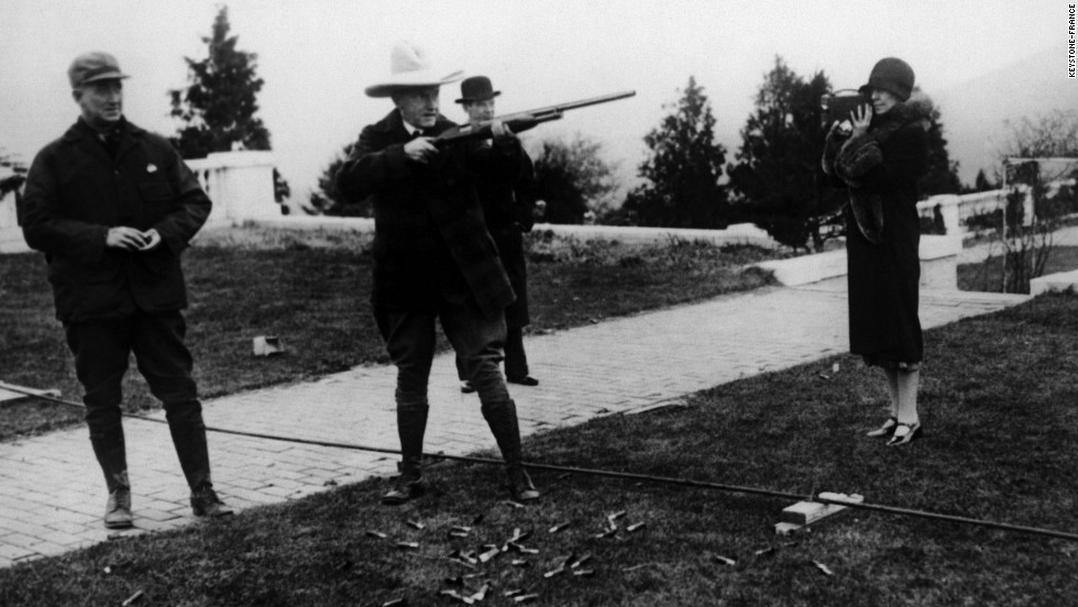 President Calvin Coolidge fires a gun as his wife, Grace Goodhue, photographs him circa 1925.