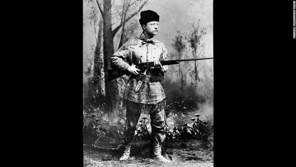 Theodore Roosevelt wields a Winchester rifle in this portrait taken in an artificial forest setting, circa 1900.
