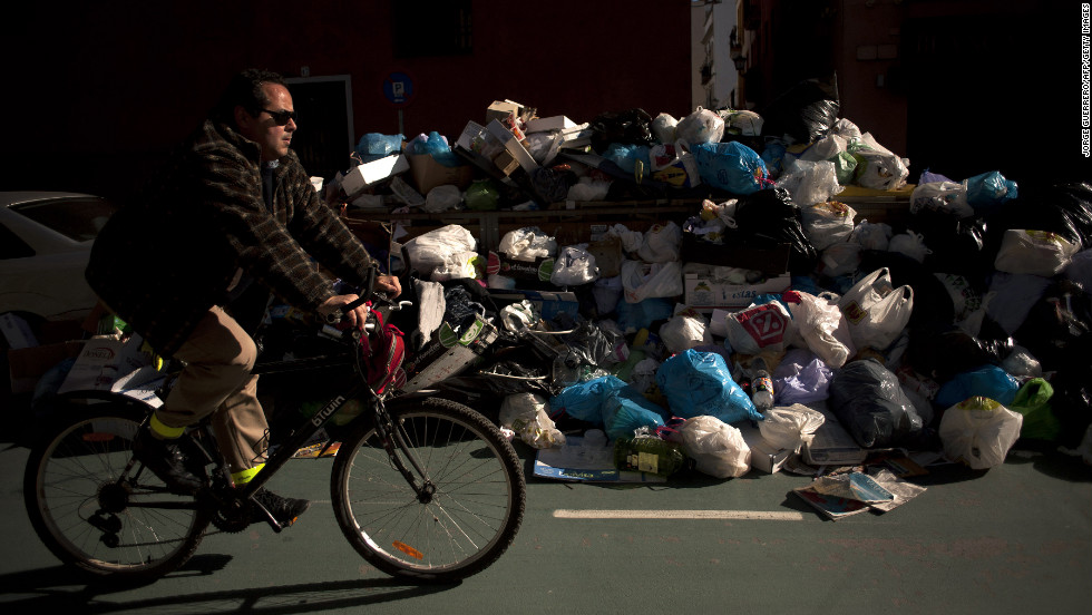 A man rides past uncollected rubbish in Seville on February 4.