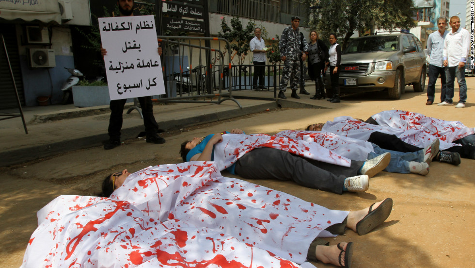 Activists participating in a flash mob don bloodied sheets as they lie in the streets outside the Ministry of Labour in Beirut to protest over violence against migrant workers. The action was held in April 2012, the month after a 33-year-old Ethiopian maid killed herself shortly after being filmed being beaten in public by a Lebanese man.