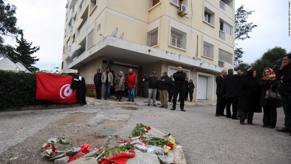 A national flag and flowers are displayed in front of the home of Tunisian opposition leader.