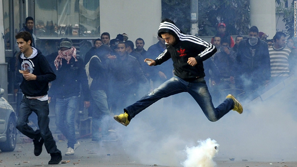 A Tunisian protester jumps amid smoke after police fired tear gas during a rally outside the Interior ministry in Tunis.