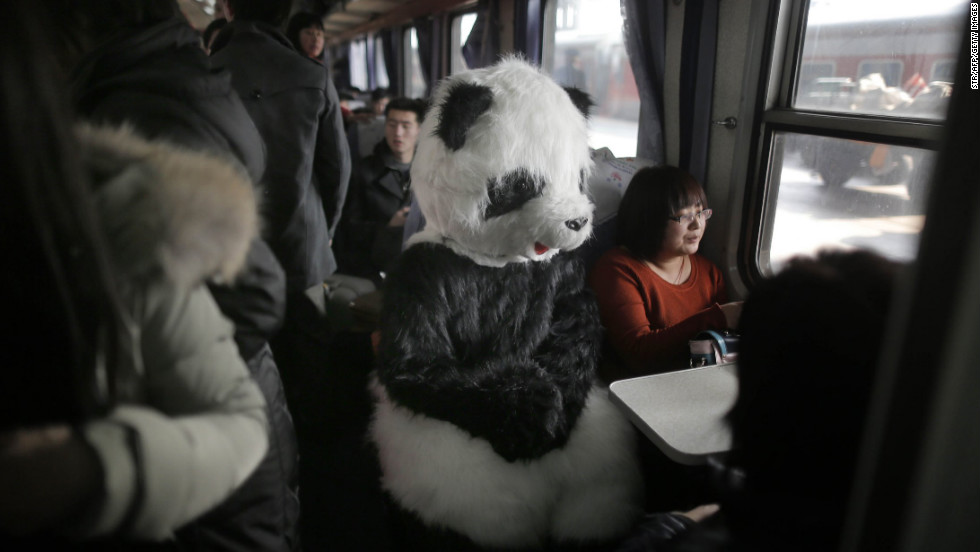 A woman in a panda costume travels with friends on a train to Cangzhou from Beijing for the Chinese New Year on January 28.