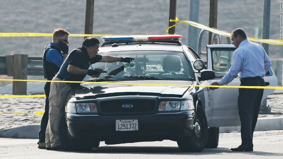 Investigators inspect a bullet-ridden squad car where a police officer was shot on Magnolia Avenue in Corona, California on February 7.