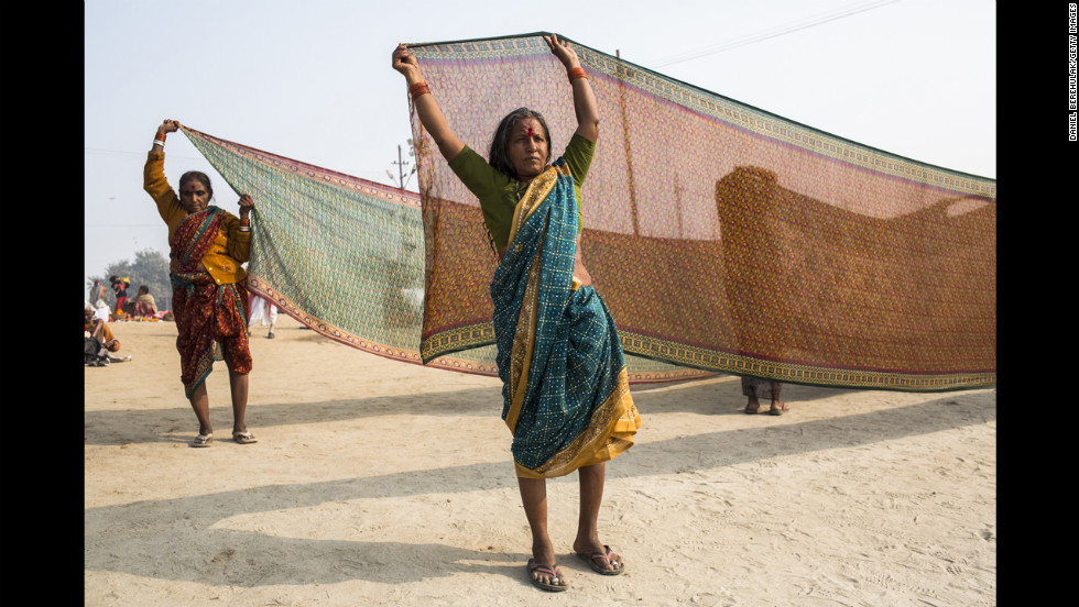 A Hindu devotee holds out a saree to dry after having bathed on the banks of the Ganges river on January 13.
