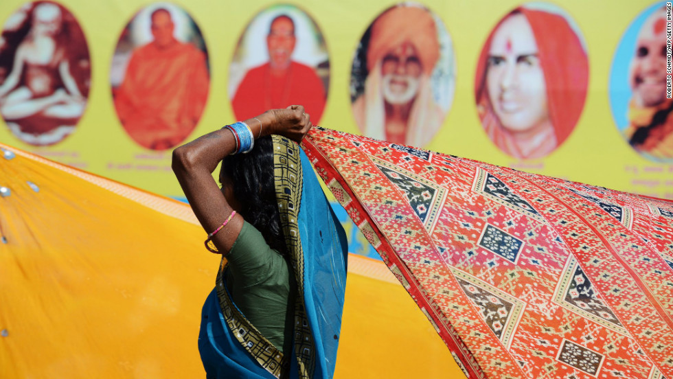 An Indian Hindu devotee dries her sari in the wind as she stands near a billboard showing Hindu gurus in  Allahabad, India, on February 8.