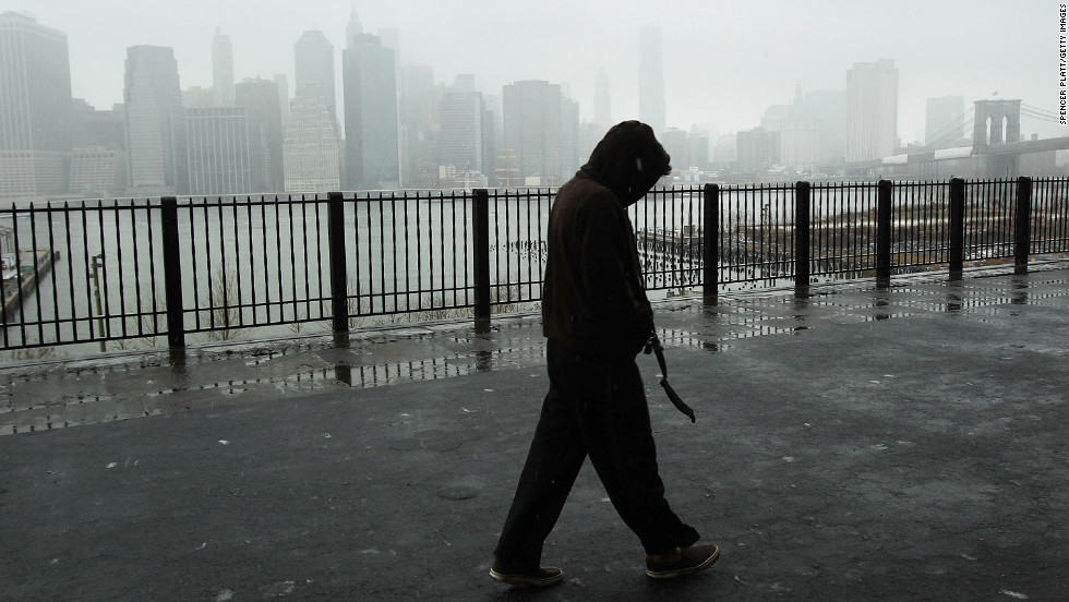 A man walks along the promenade in Brooklyn Heights as Lower Manhattan stands in a cloud of snow and sleet in the early hours of a major winter storm on February 8.