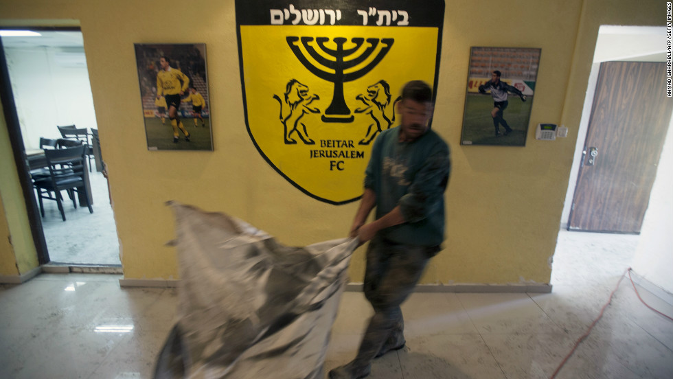 A club official at Beitar Jerusalem cleans up after the arson attack on the club's offices.