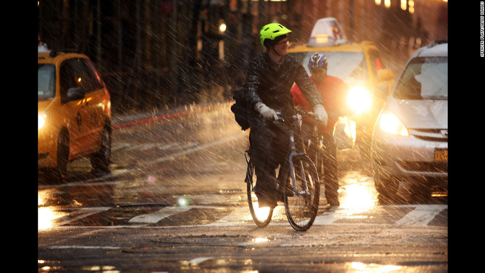 Bicyclists wait at a light in wind, snow and sleet on Friday.