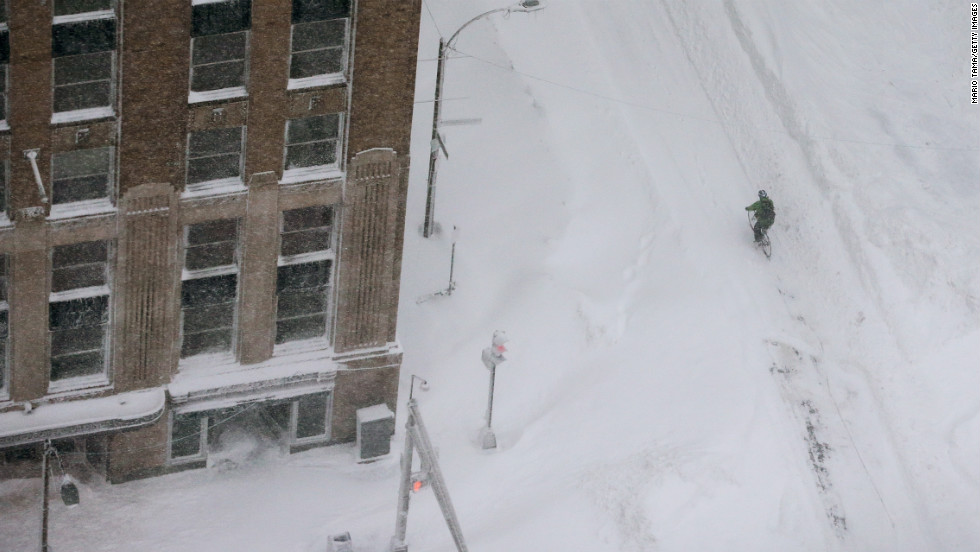 A cyclist rides through the snow in the Back Bay neighborhood of Boston.