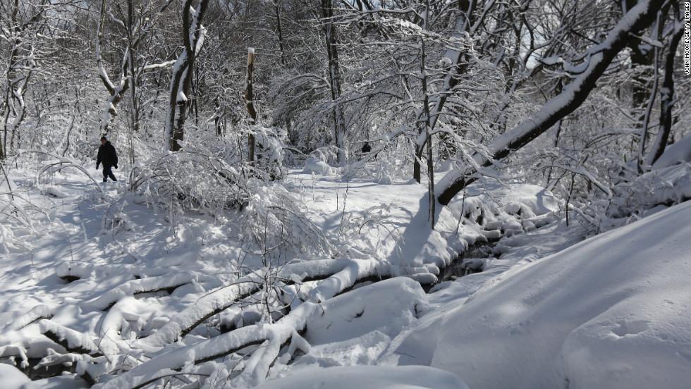 A man walks along a snow-covered trail in Central Park on Saturday.