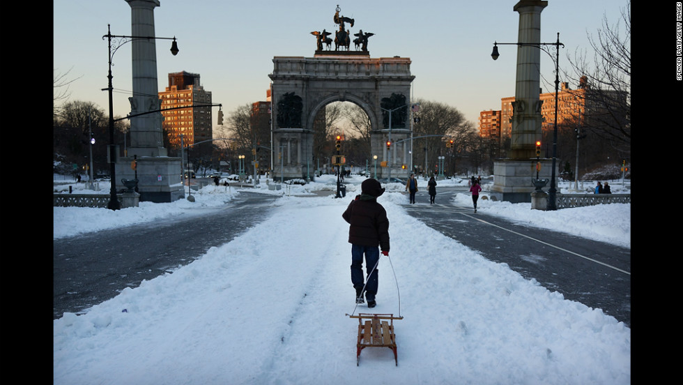 A boy pulls a sled through a snowy Prospect Park in Brooklyn on Saturday.