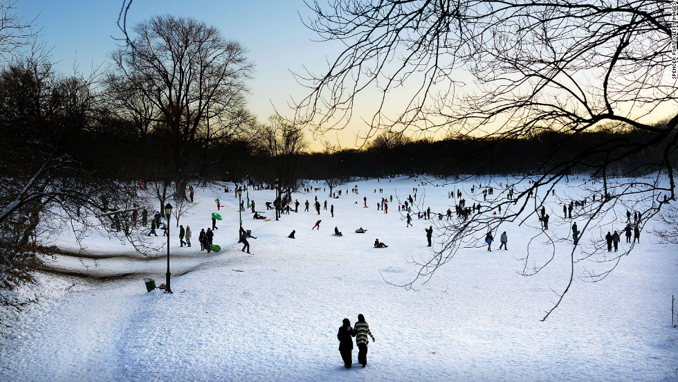 People walk and sled through a snowy Prospect Park in Brooklyn, New York, on Saturday.