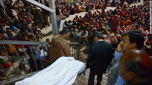 Indian authorities remove the body of a person  killed during a stampede at the railway station in Allahabad on Sunday.