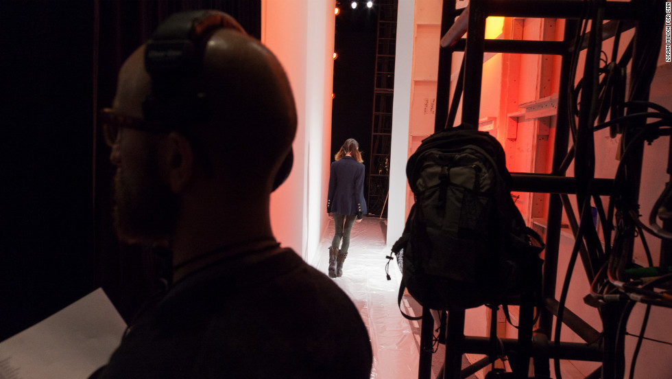 A model and a crew member are seen backstage near the entrance to the runway on February 10.