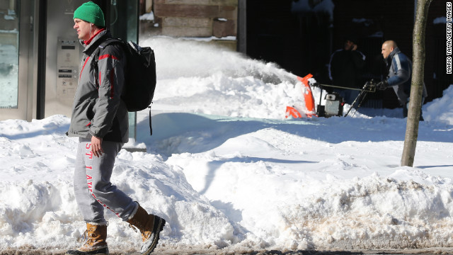 A man walks by as another clears snow from a sidewalk Saturday in the Back Bay neighborhood of Boston.