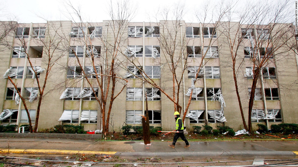 An electrical crew worker walks past a building with blown-out windows across from the University of Southern Mississippi in Hattiesburg on February 11. Dozens of people were injured in the storm in the Mississippi town.