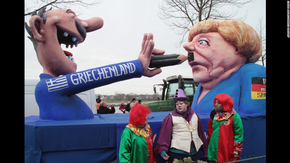 Clowns stand in front of a float featuring a Greek man painting a moustache on German Chancellor Angela Merkel during the carnival parade in Düsseldorf.