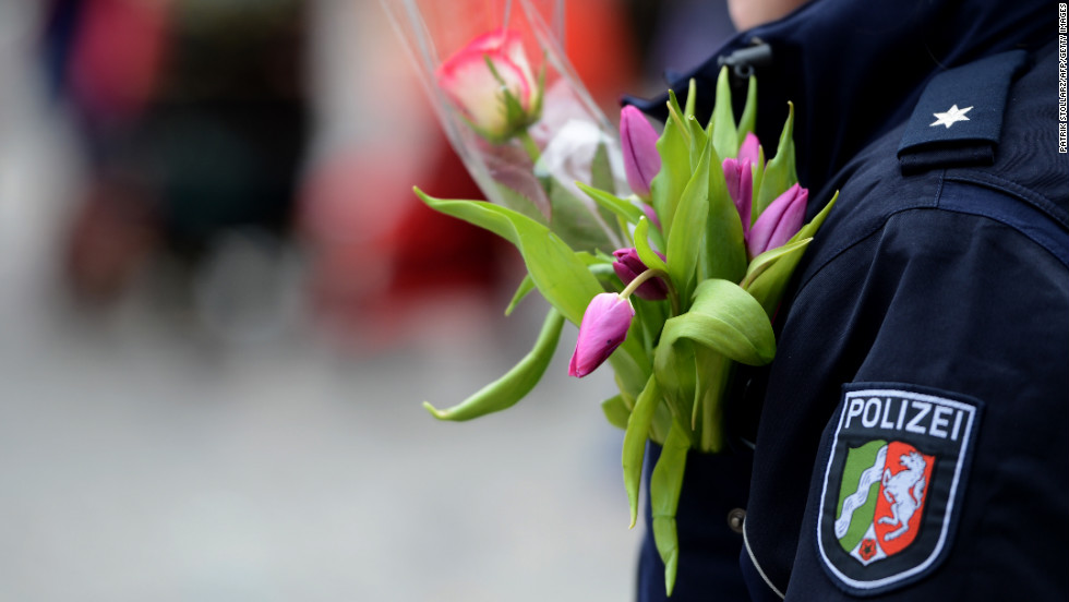 A policewoman in Düsseldorf wears flowers on her jacket.