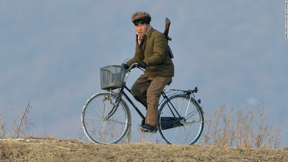 A North Korean soldier rides a bike beside a river crossing on the Yalu River near the North Korean town of Sinuiju on February 12, 2013.