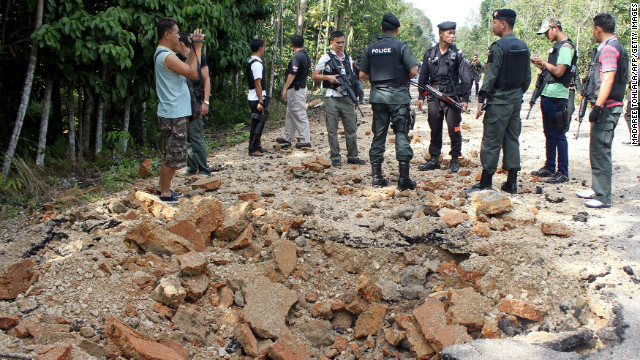 Policemen inspect a bomb site in the southern province of Narathiwat on Sunday, part of a recent wave of separatist violence.