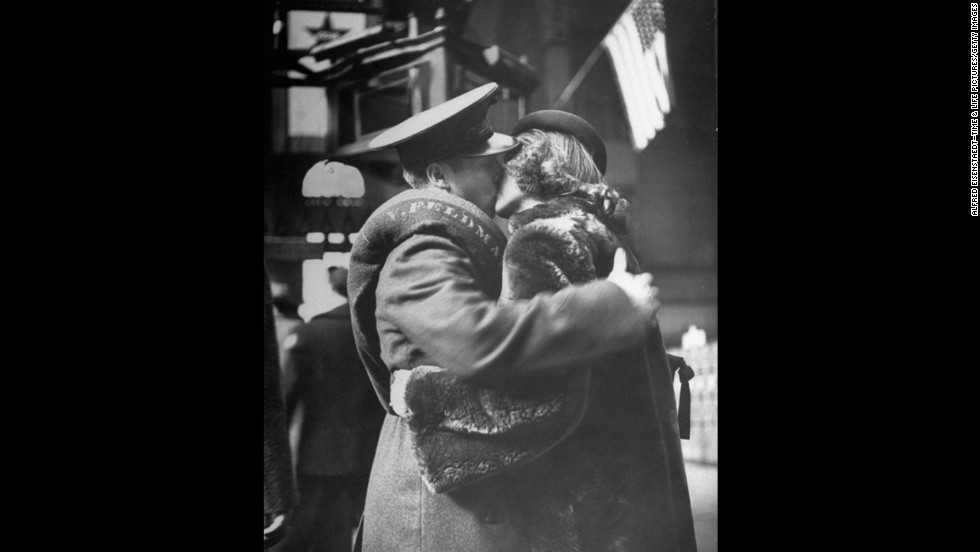 An American flag waves behind them as a couple kiss goodbye. In celebration of Valentine's Day, here are images of couples kissing goodbye as soldiers depart New York's Penn Station for World War II in April 1943.