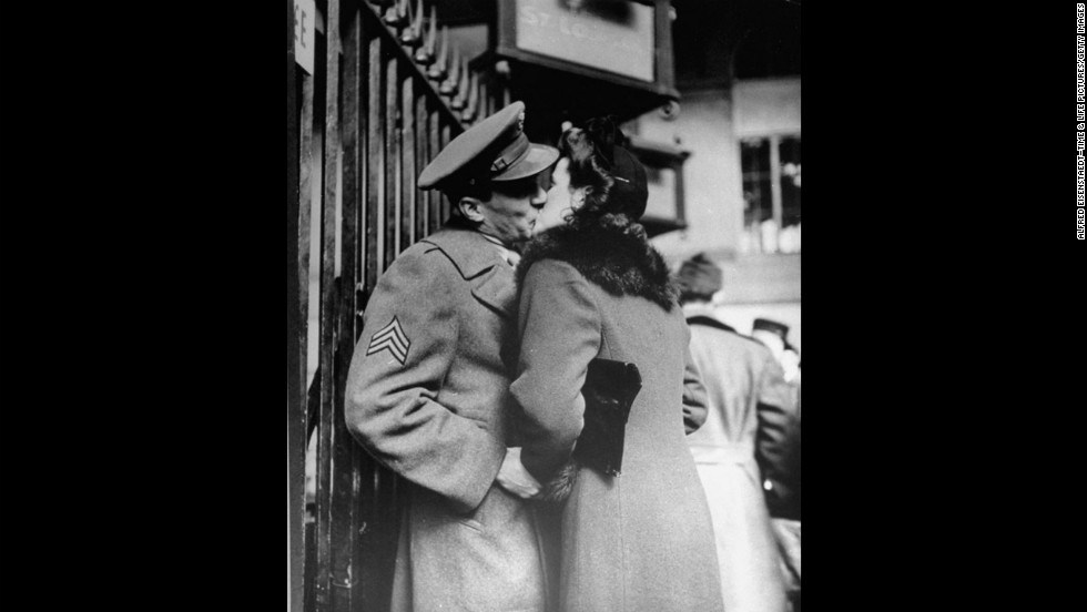 Clasping his hands, a woman kisses her beau before he departs.