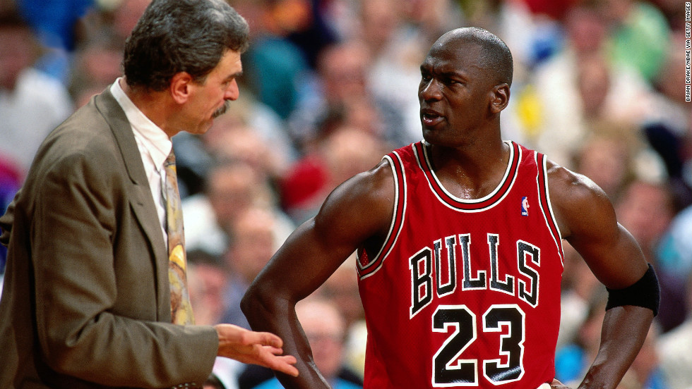 Jordan and former Bulls head coach Phil Jackson talk during a game in 1991.