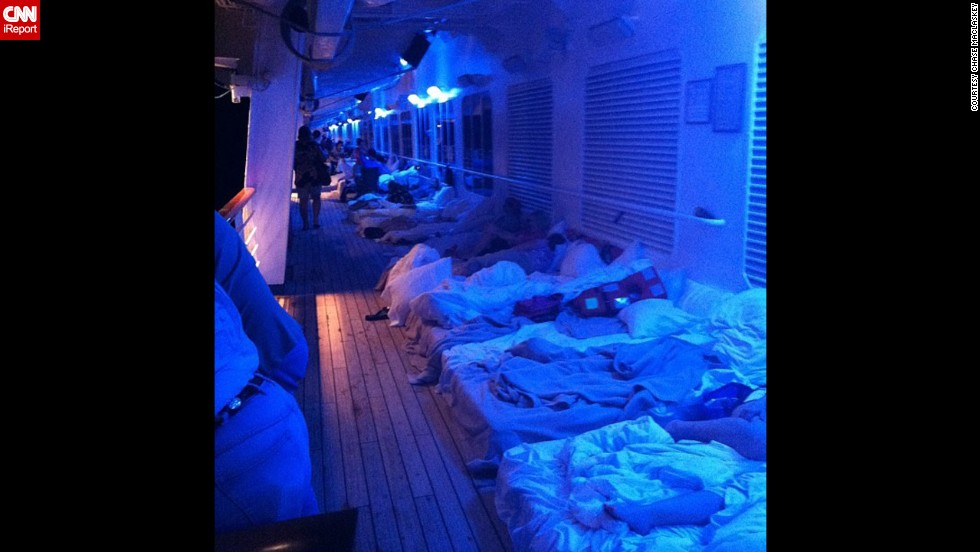 Passengers set up makeshift beds on a deck of the ship.