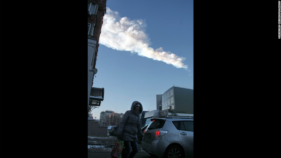 The meteor's vapor trail passes over the city.
