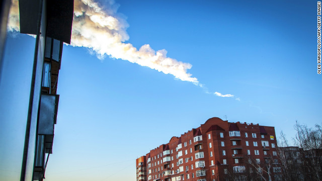 The trail of a falling object is seen above a residential apartment block in the Urals city of Chelyabinsk. A heavy meteor shower rained down today on central Russia, sowing panic as the hurtling space debris smashed windows and injured dozens of stunned locals, officials said.