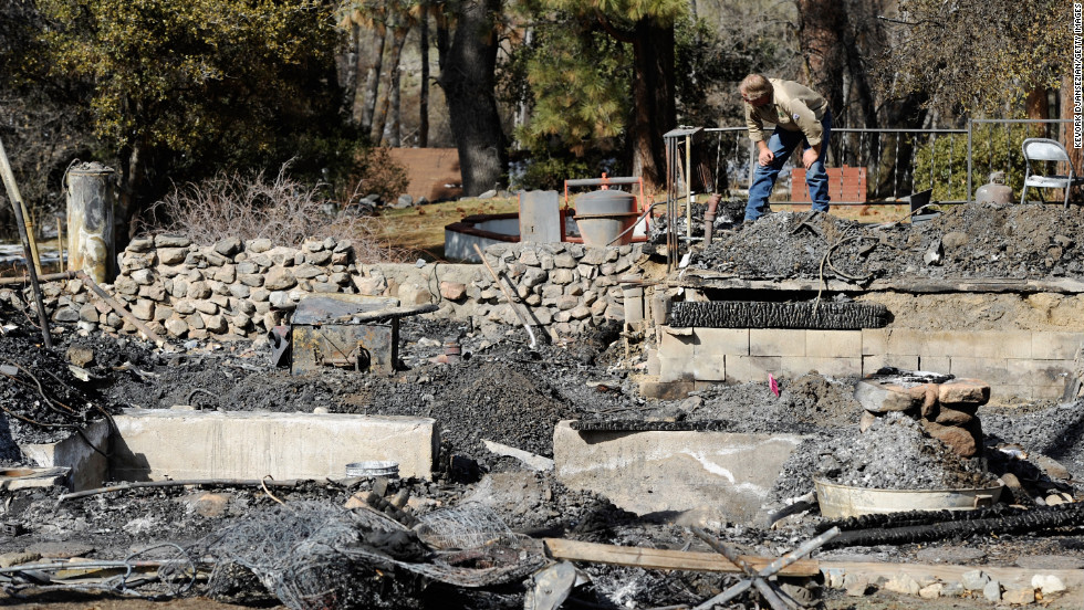 An employee of Southern California Edison surveys the damage at the burned-out cabin where the remains of multiple-murder suspect and former Los Angeles Police Department officer Christopher Dorner were found on Friday, February 15, in Big Bear, California.
