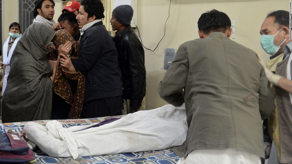 Mourners stand near a relative killed in the blast.