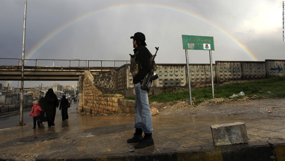 A member of the Free Syrian Army stands with his weapon as he looks at a rainbow in Aleppo on February 16.