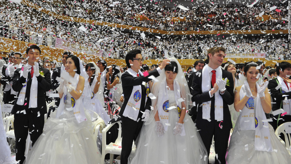 Confetti falls on the newly married couples.