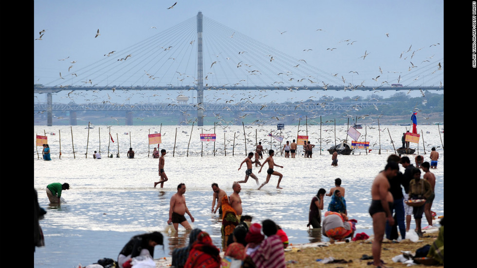 Young men run in the waters of the Sangam as Hindu devotees bathe on Saturday, February 16.