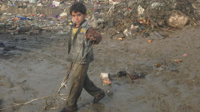 A young boy searches through refuse for sellable items in a garbage dump in Sadr City, Iraq