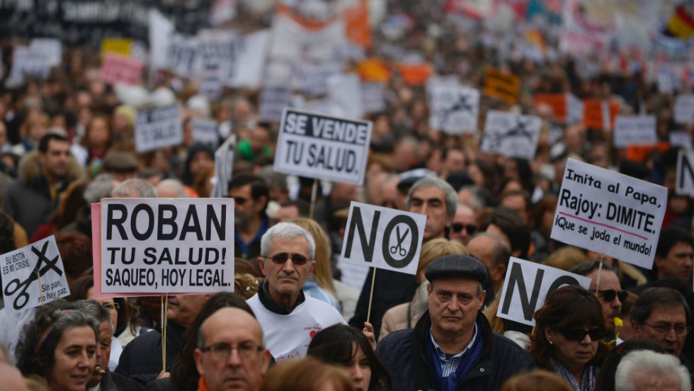 Protesters hold placards as they take part in a demonstration against plans to cut medical spending and privatize hospital services in Madrid on February 17.