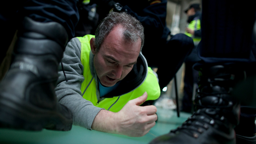 Policemen arrest a Spanish Airline Iberia worker during a protest against job cuts at Barajas Airport on February 18 in Madrid, Spain.