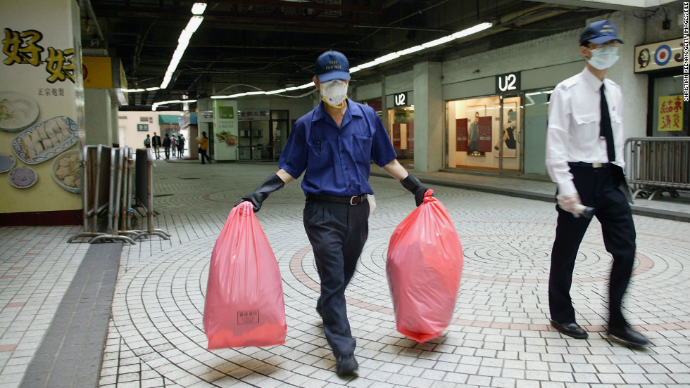 A government worker carries a bag of personal items to be cleaned from the Amoy Gardens housing complex on April 2, 2003. More than 300 people were infected at the complex. Of those, 42 died.