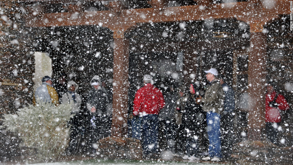 Golf fans seek shelter from the snow Wednesday after the first round of the Accenture Match Play Championship at Dove Mountain in Marana, Arizona. The tournament was suspended due to the weather.