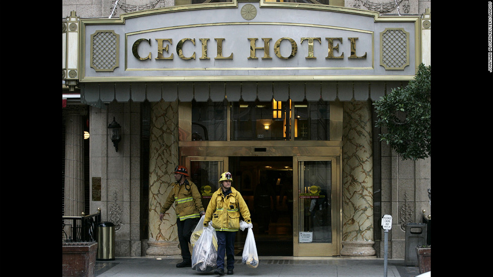 Firefighters leave the Cecil Hotel after removing the body.